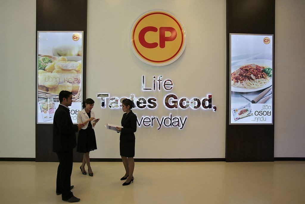 Charoen Pokphand Foods Pcl (CP Foods) employees talk in front of signage displayed at the company's plant in Chok Chai, Nakhon Ratchasima province, Thailand.